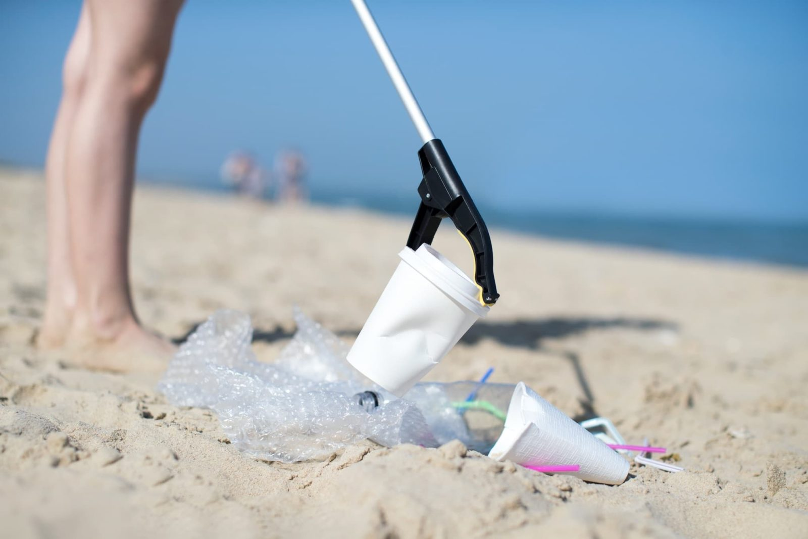 man using litter picker for rubbish on a beach