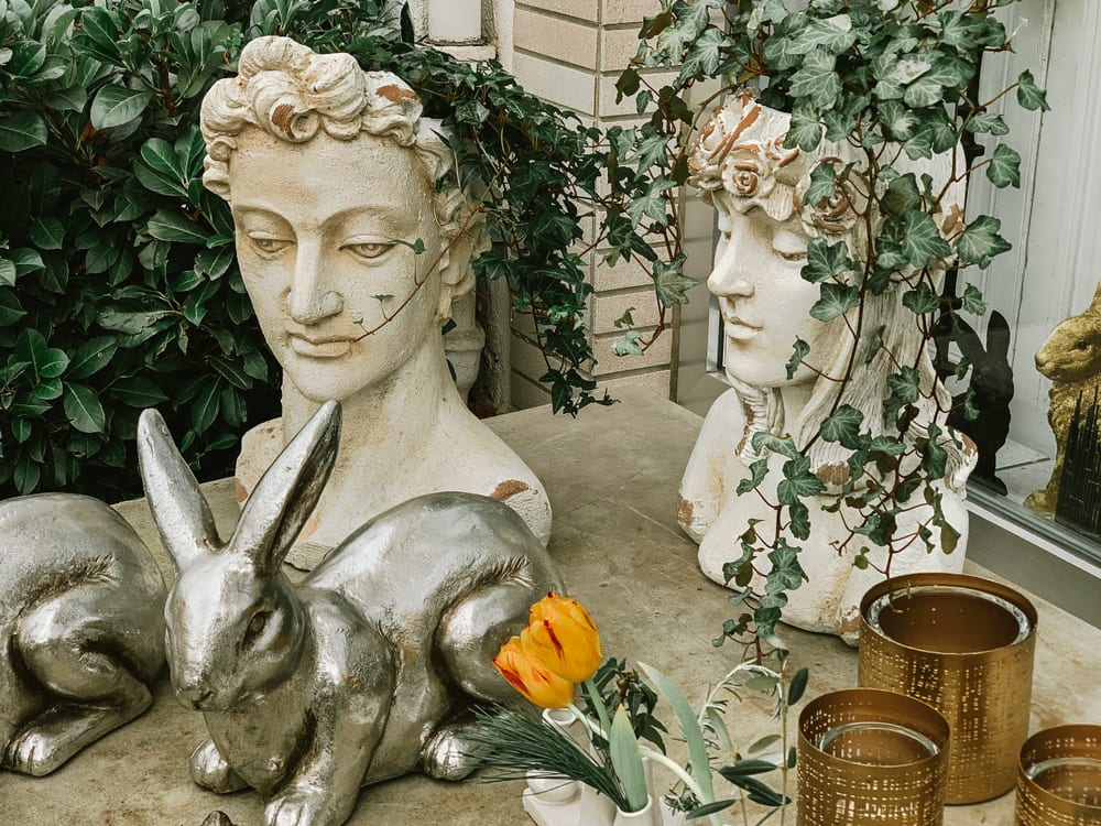 greek statues with ivy growing from their heads