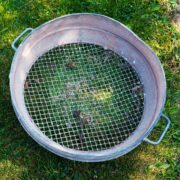 an old metal garden sieve sat on a lawn