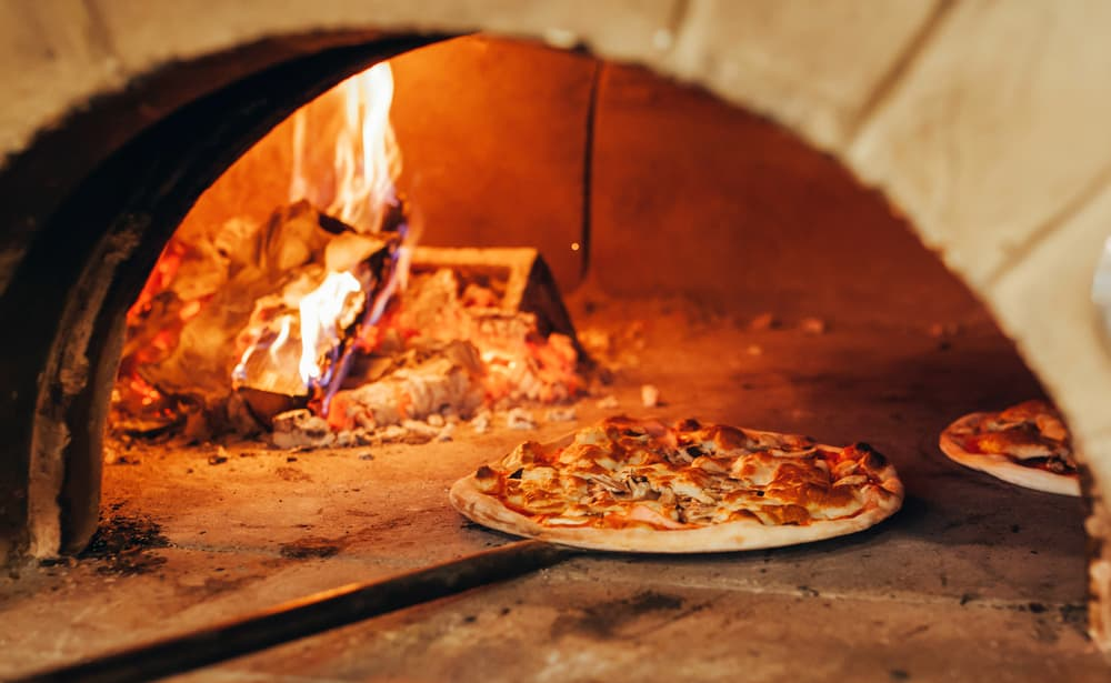 pizza cooking in a woodfire oven