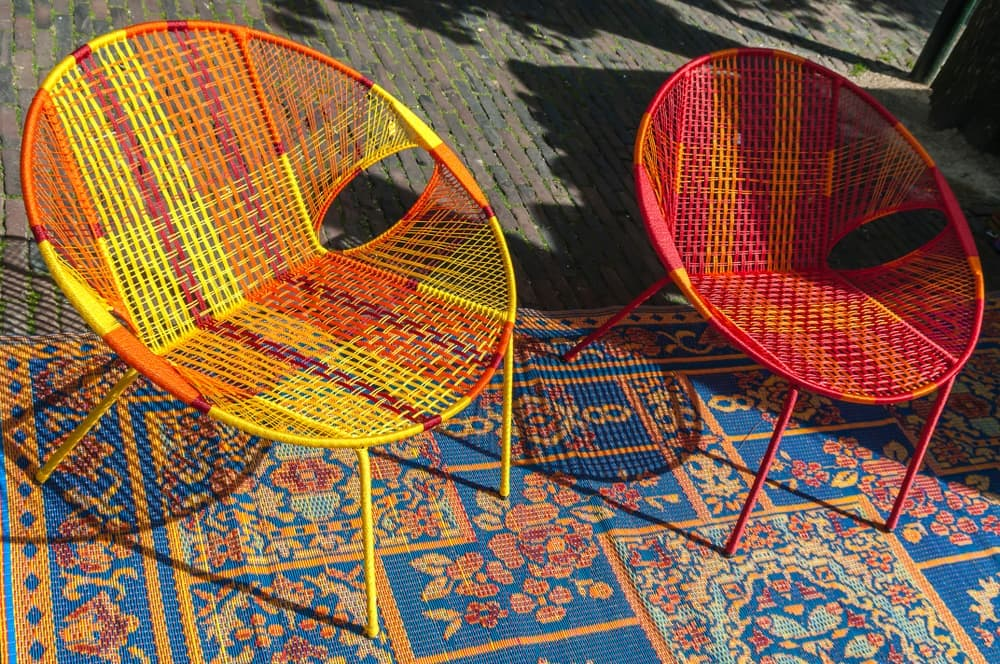 a garden rug and colourful rattan chairs