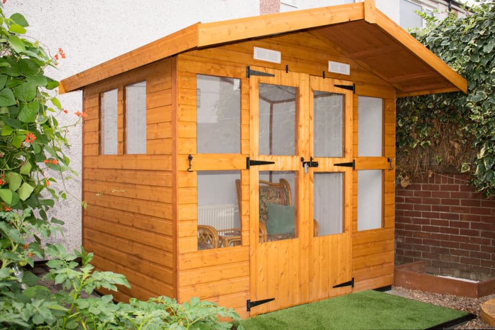 a wooden shed in the corner of a garden