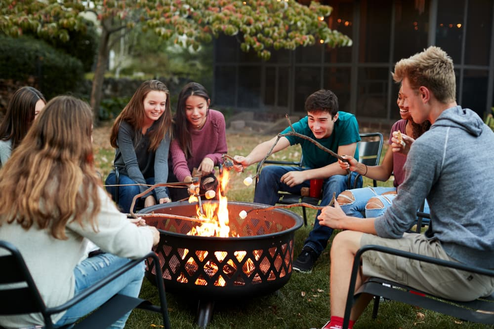 a garden fire pit with young people sat around