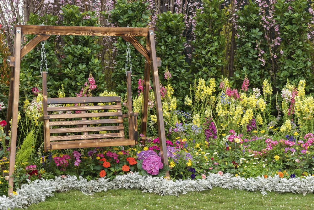 a garden bench swing with flowers in the background