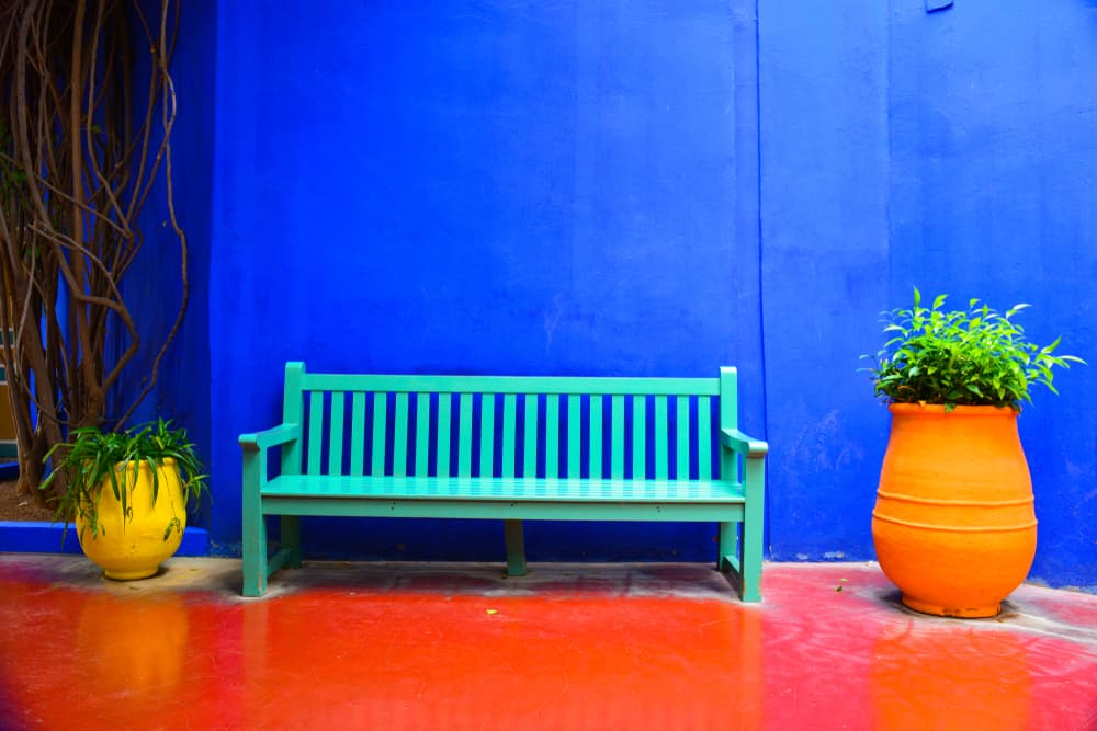 a moroccan courtyard with a bench and planters