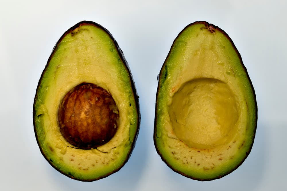 an avocado in two halves on a white background