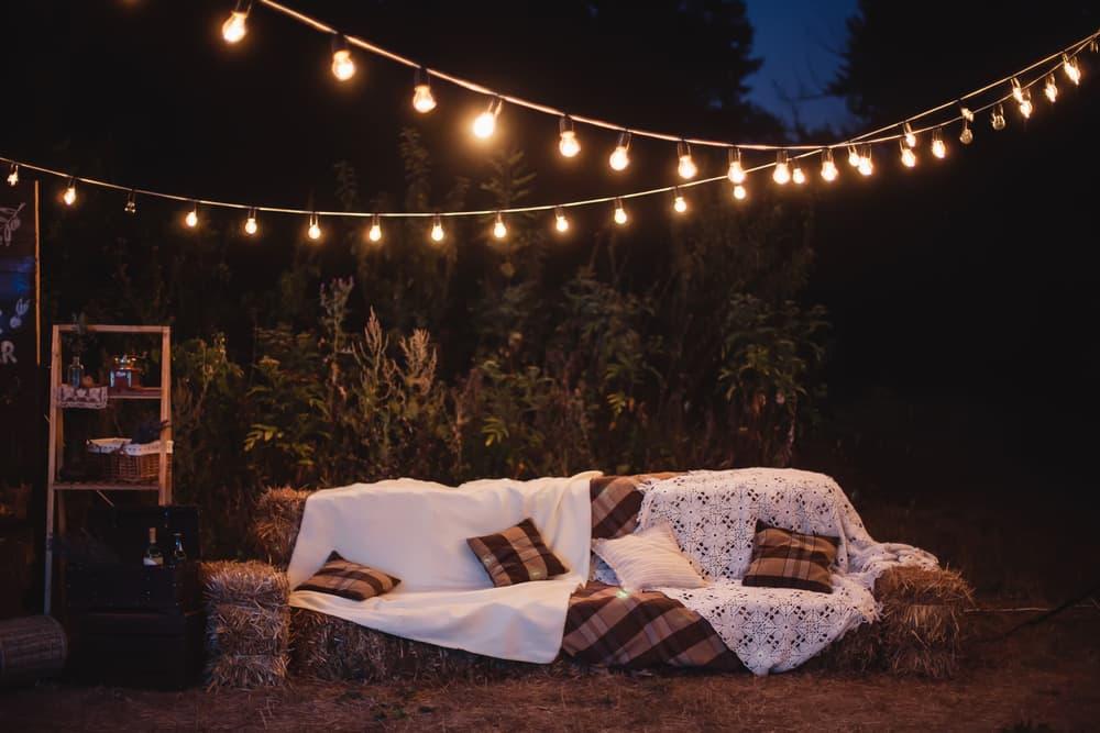 hanging lights above a garden sofa