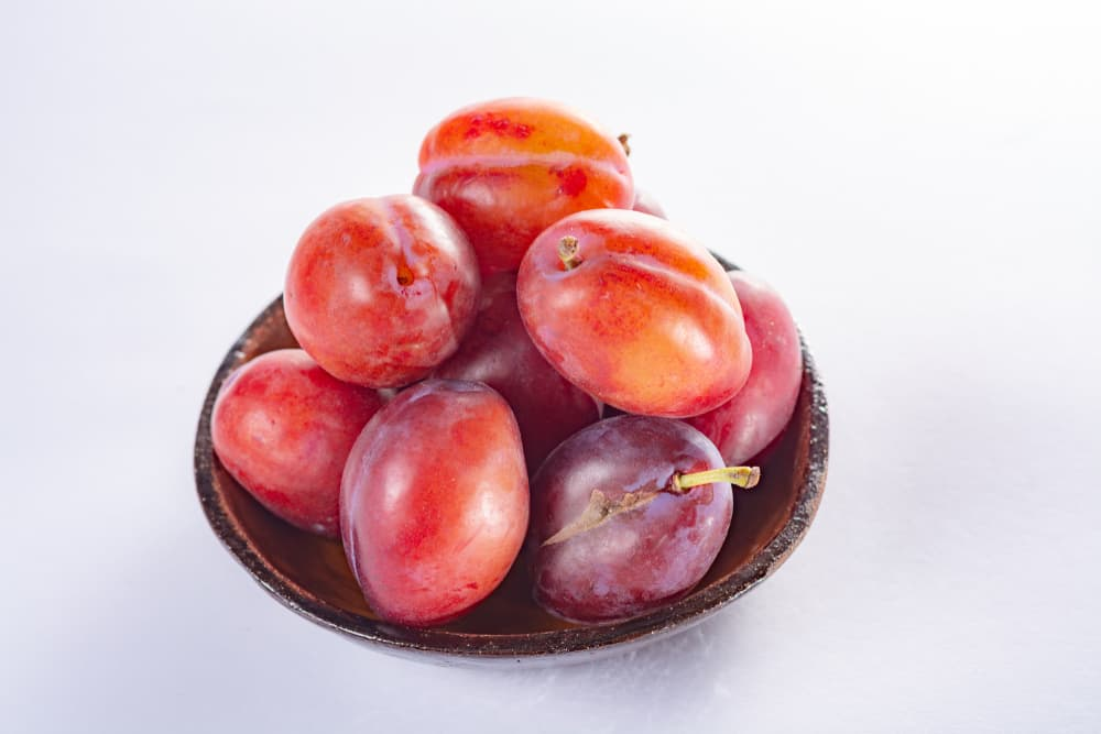 victorias in a bowl on a white surface