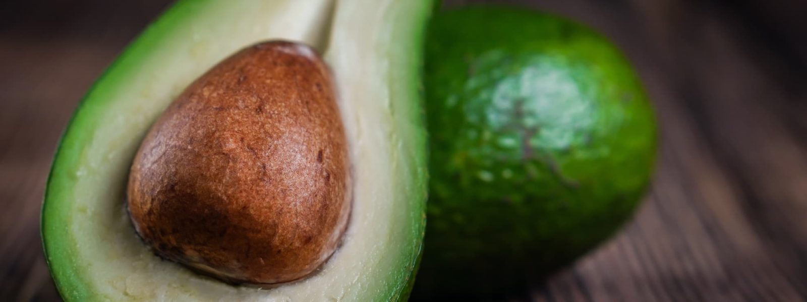 an avocado sliced in half showing its stone