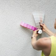 woman comparing paint colours on home exterior wall