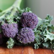 organic purple sprouting broccoli on wooden countertop