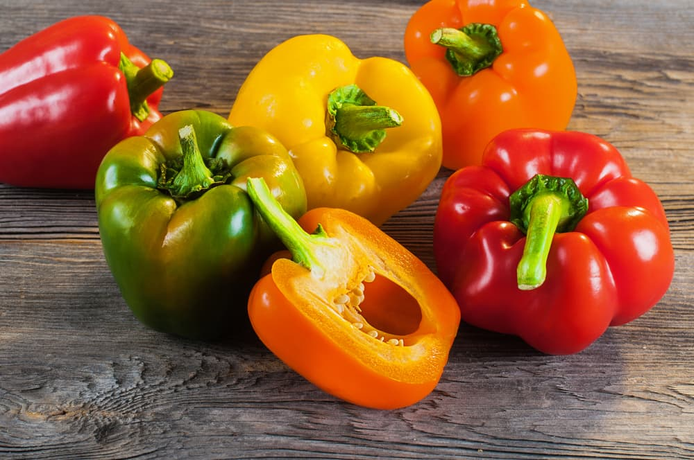 mixed coloured peppers on a wooden countertop