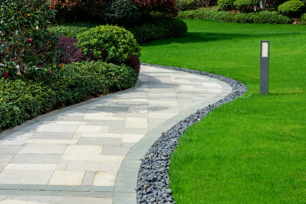 a winding path with grass, gravel and borders either side