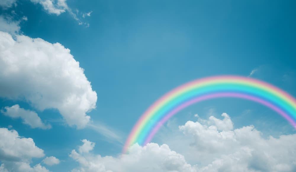 a rainbow, clouds and blue sky