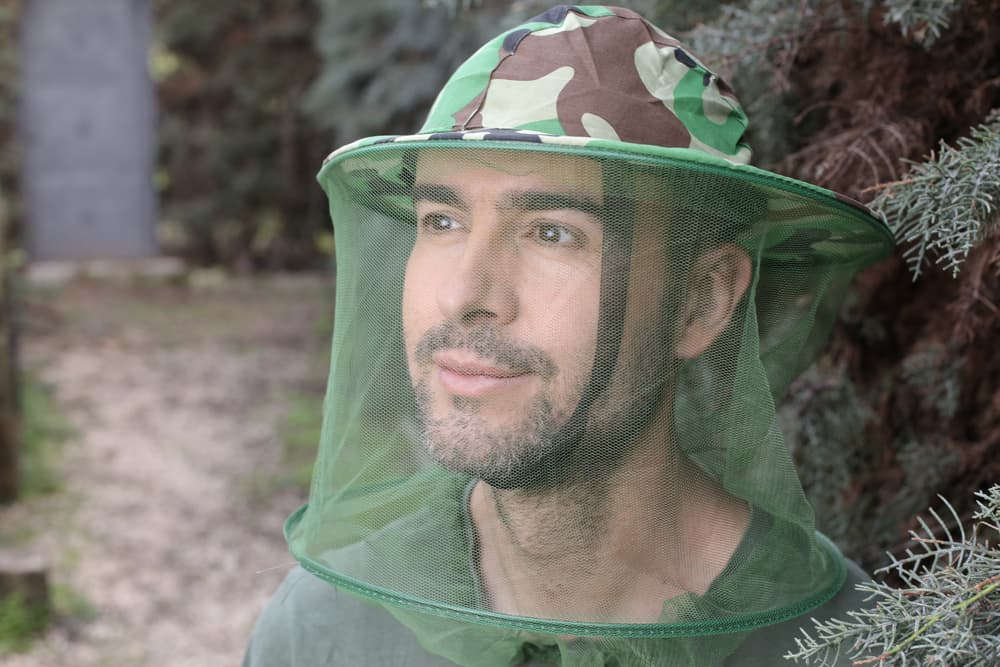 man wearing a insect head net outdoors