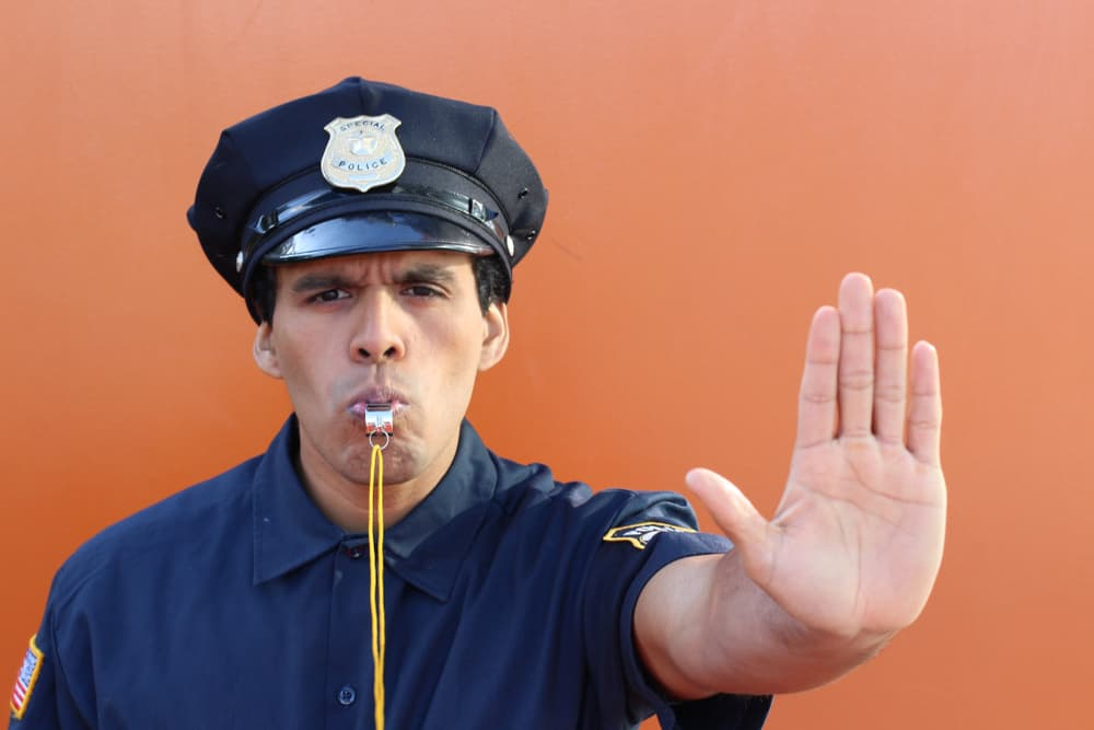 policeman holds hand out in stop motion on orange background