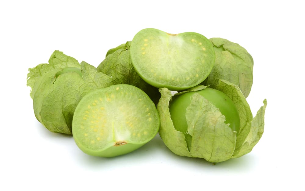 green tomatillos with their husks on a white background
