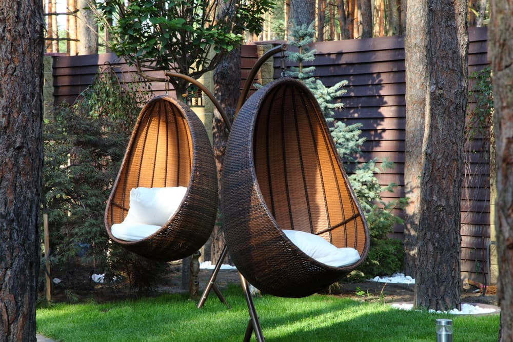 two rattan hanging egg chairs in a modern garden