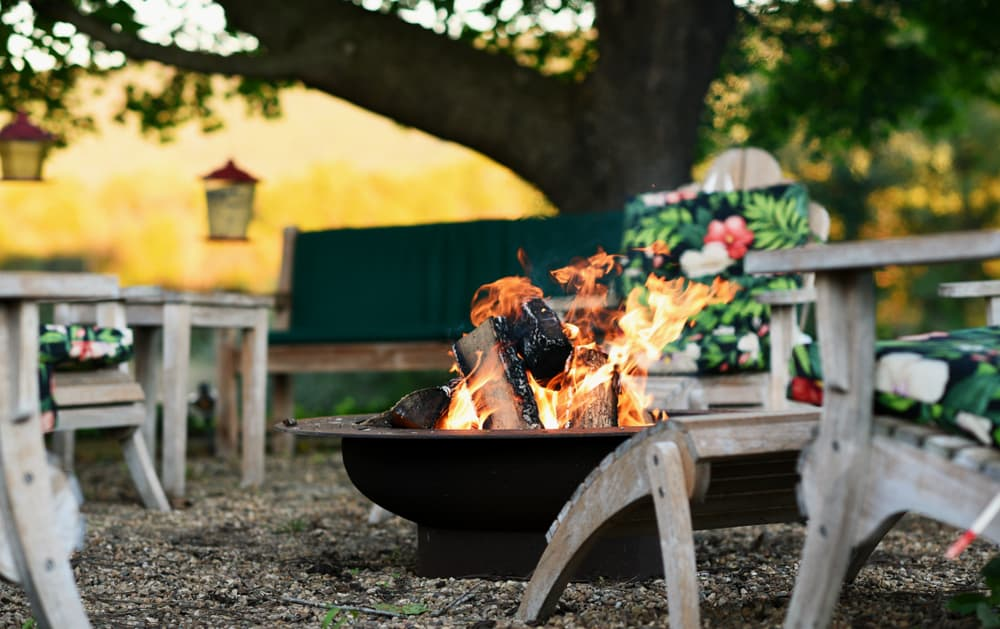 a fire pit in the centre of wooden garden furniture