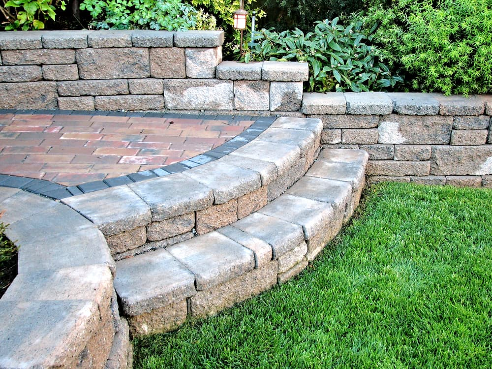two rounded steps leading to a garden lawn