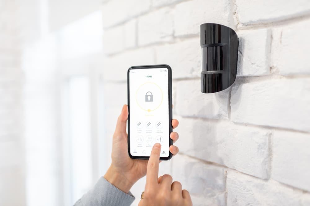 human hands controlling a smartphone motion detector alarm