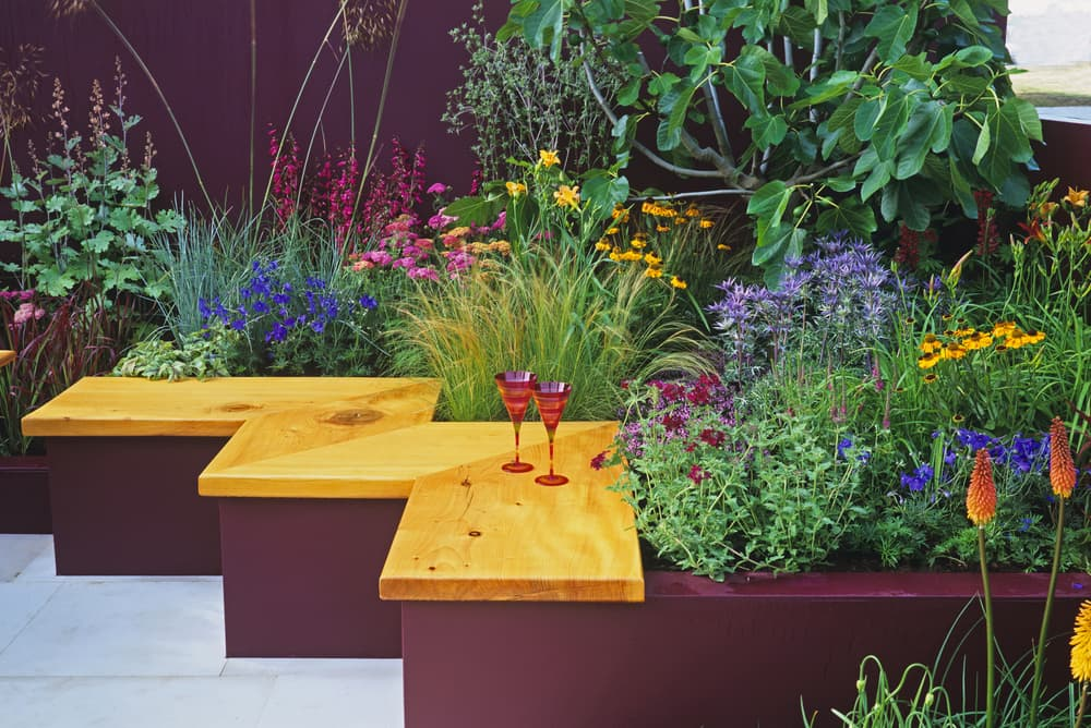small seating area with colourful flowers in a garden bed