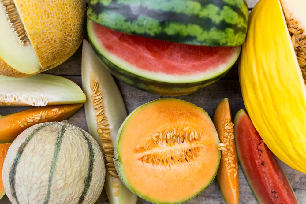 many different types of melon sat on a table