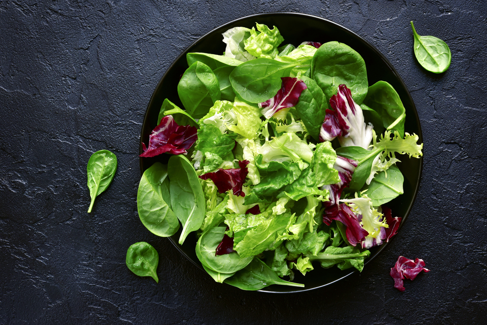 mixed salad leaves in a black bowl on a stone surface