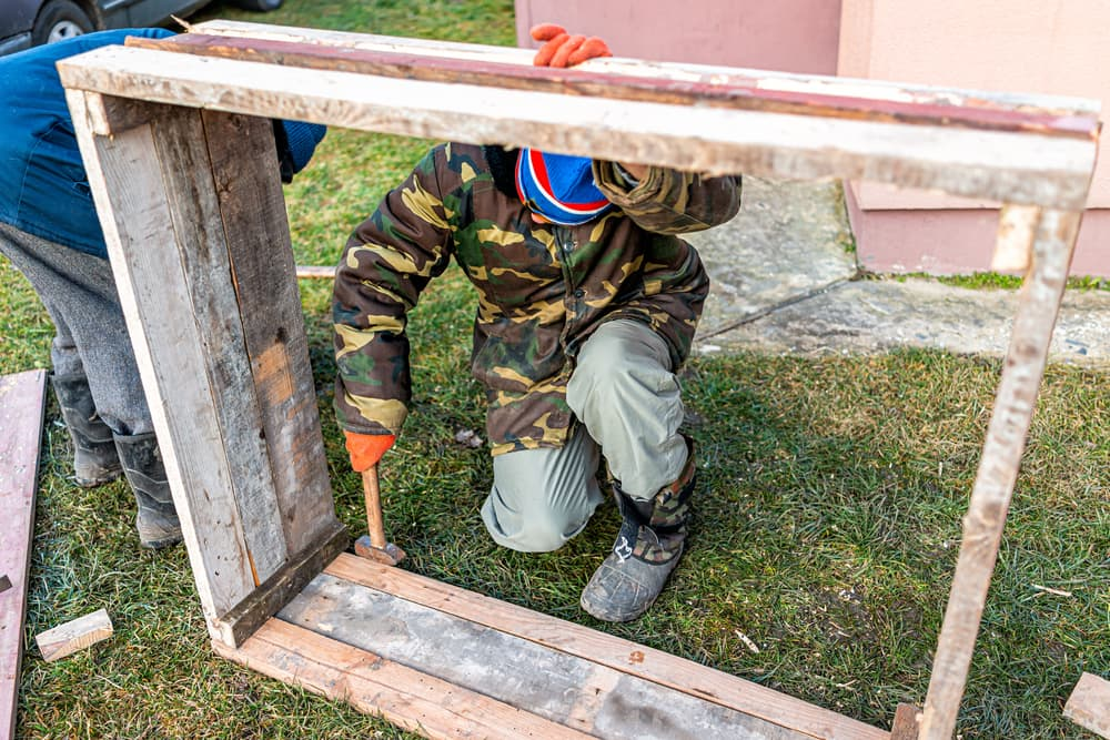 man in camo jacket using a hammer to construct a cold frame