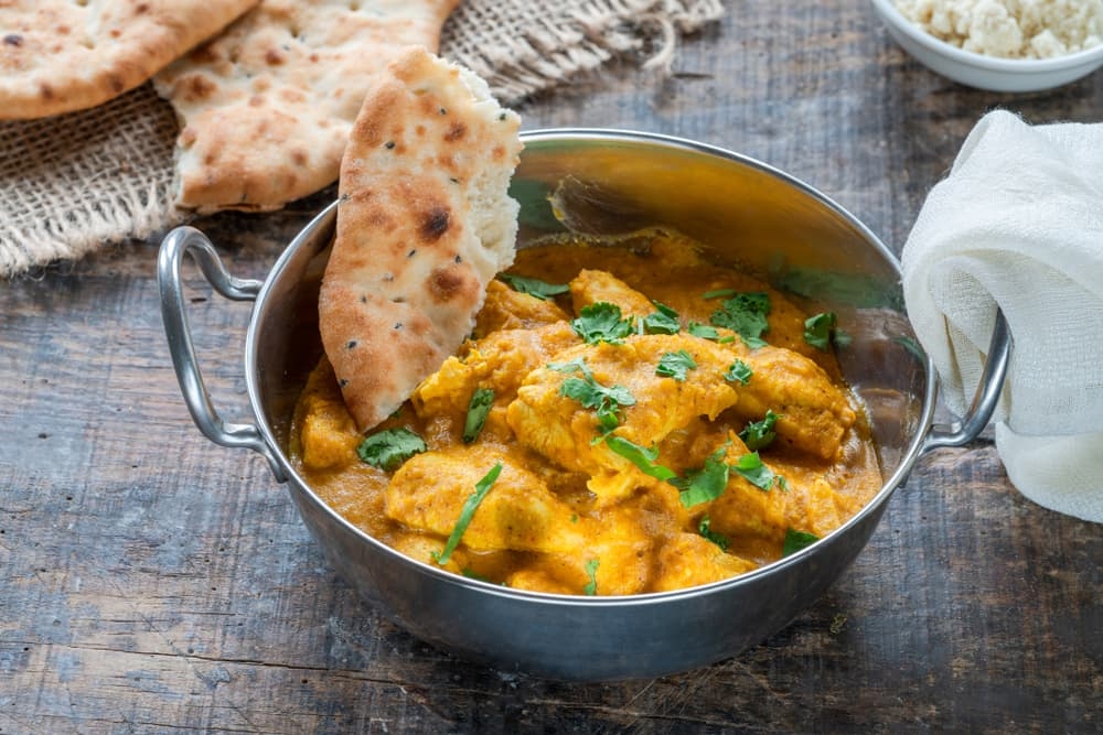coriander sprinkled on a chicken korma curry with naan