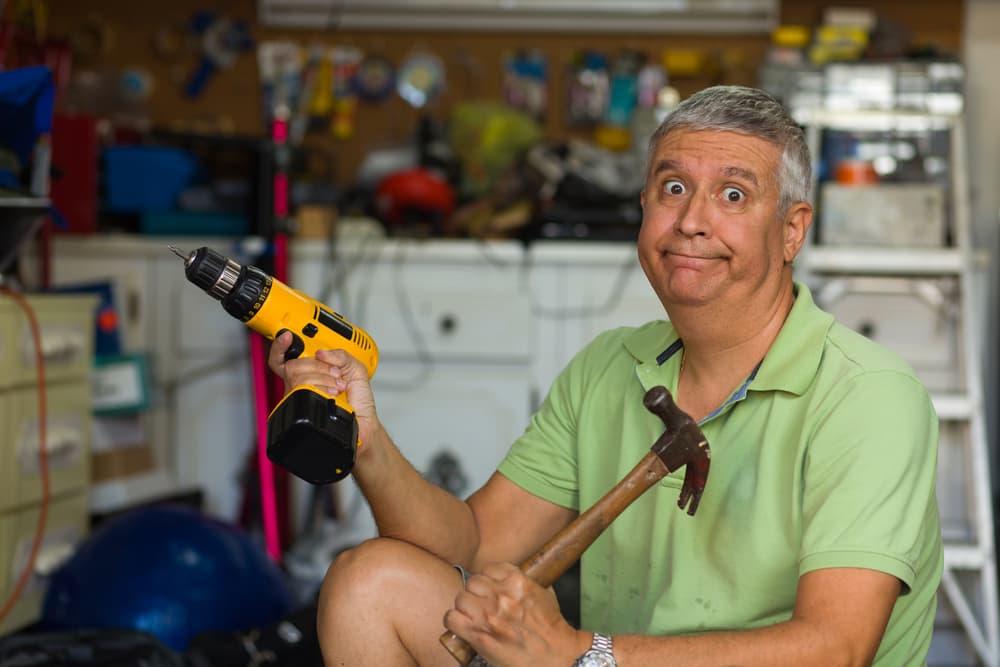man holding DIY tools looking confused