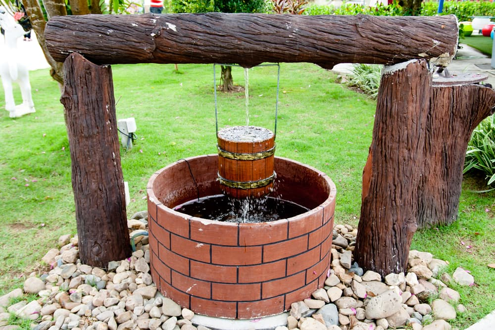 an artisan well surrounded by rocks and tree trunks