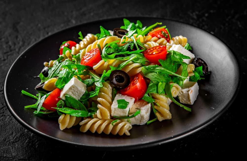 pasta, olives, feta, rocket and tomato salad on a black plate