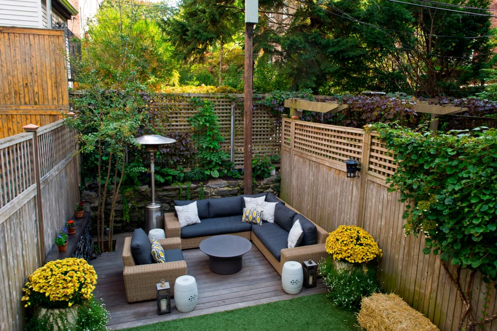 an outdoor living space at the end of a garden