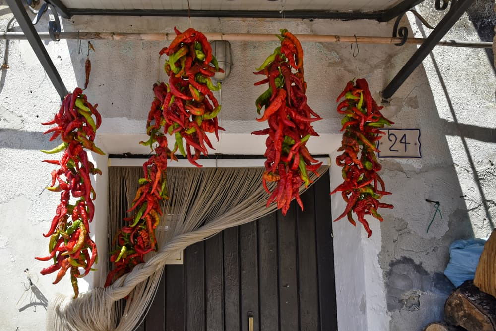 red chillies hanging to dry on the doorstep of a property