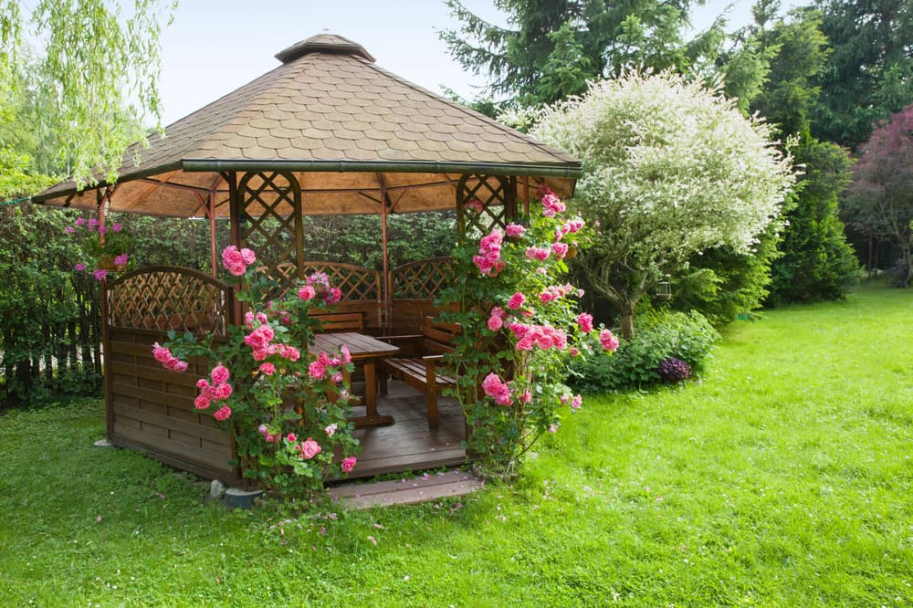 a garden gazebo with furniture and pink roses growing up the outside