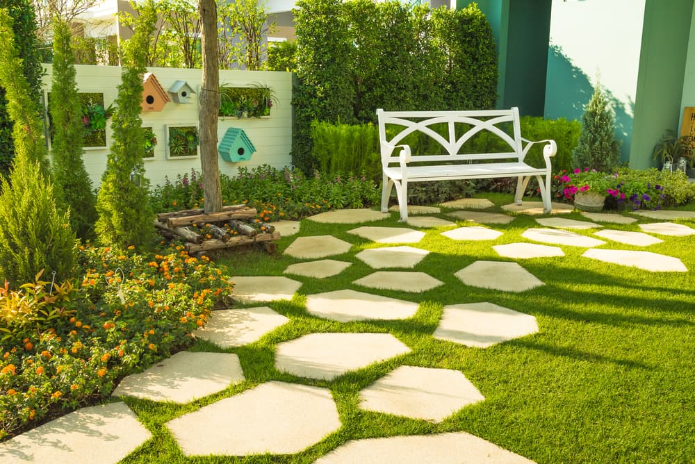 white wall and white wooden bench with patio slabs in various sizes, shapes and positions