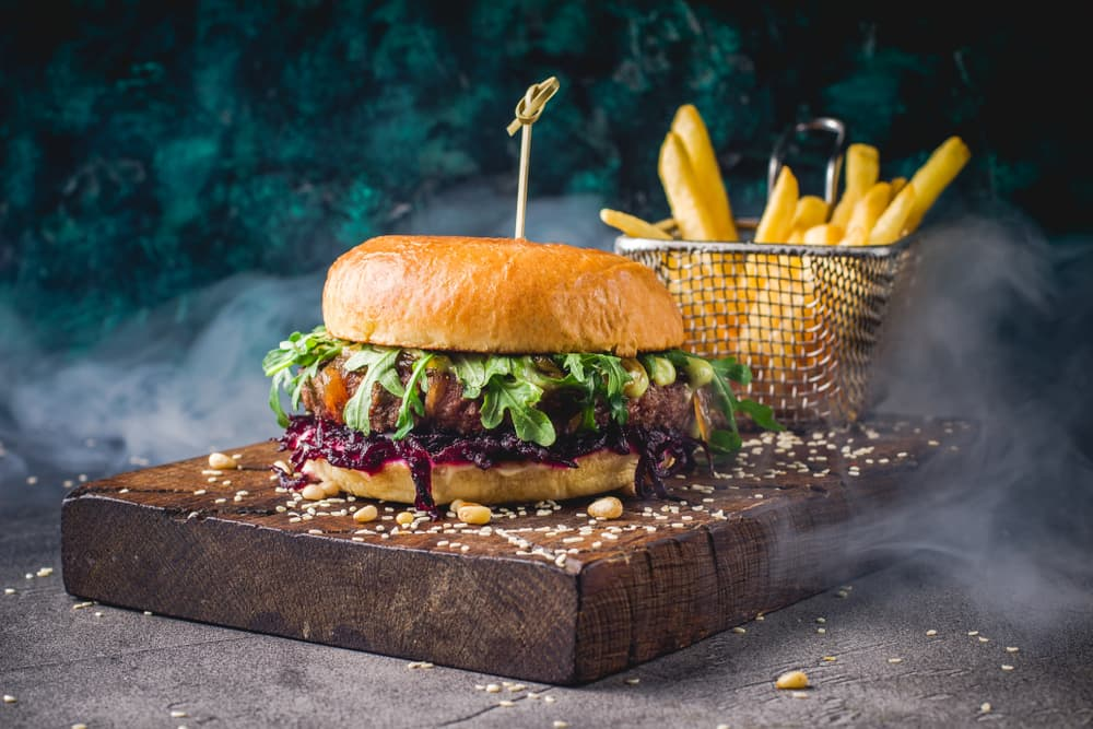 beef burger and fries on a wooden tray