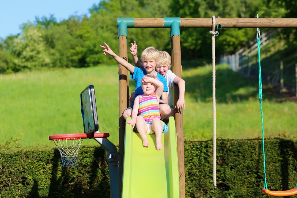 three children at the top of a garden slide