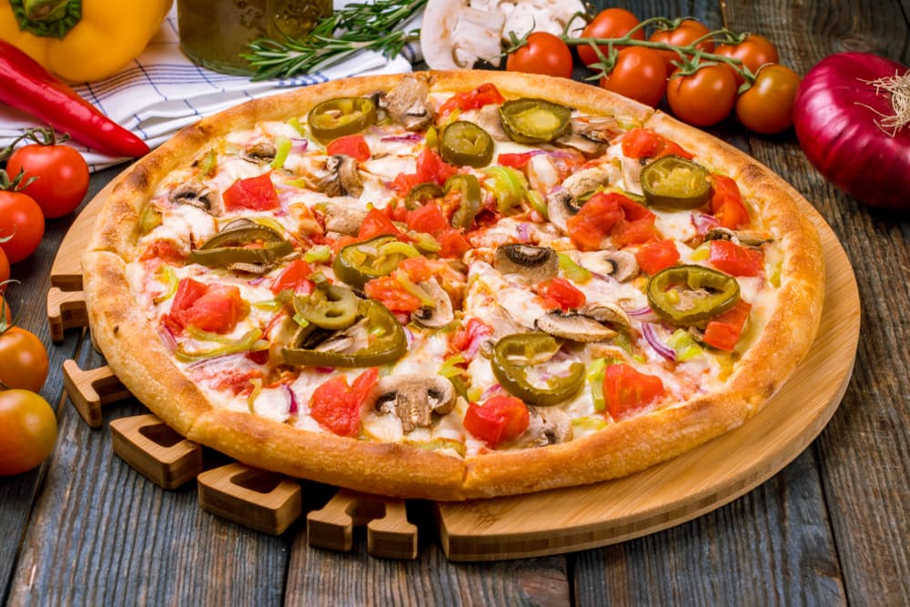 pizza laid on a wooden table with meat and jalapenos