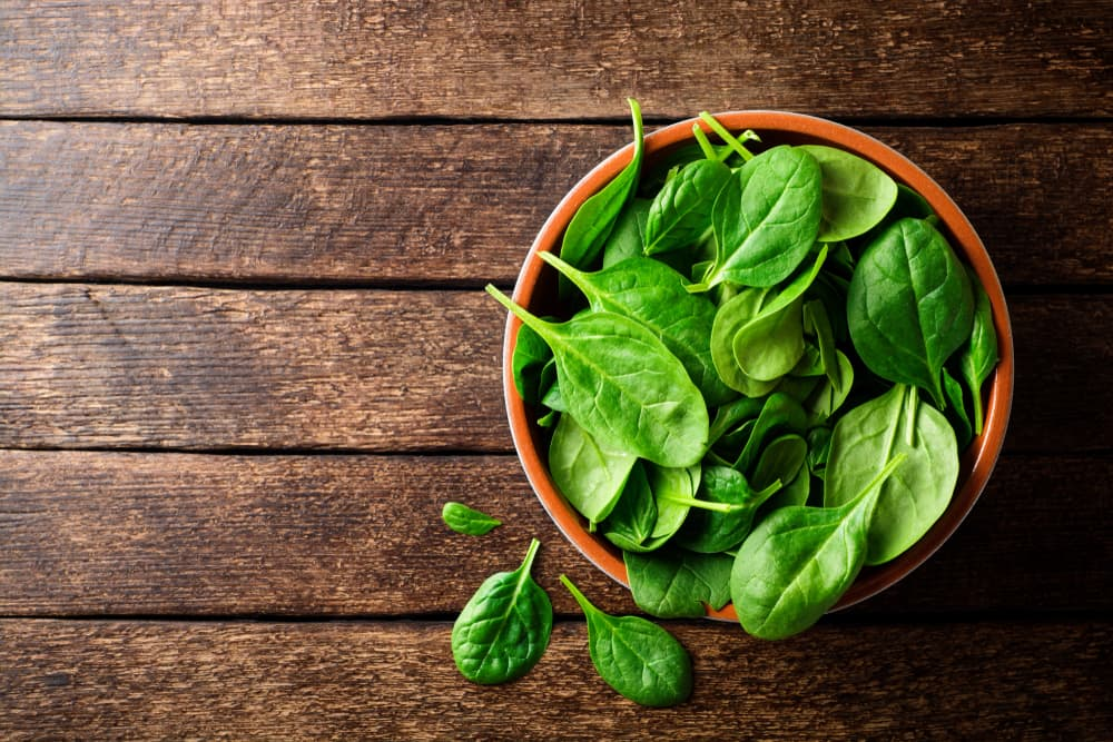 spinach leaves in a ceramic bowl on a wooden worktop