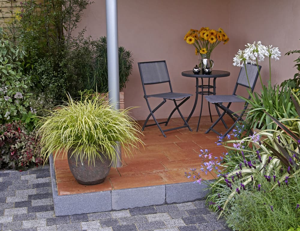 carex in a stone planter with garden furniture on a patio area