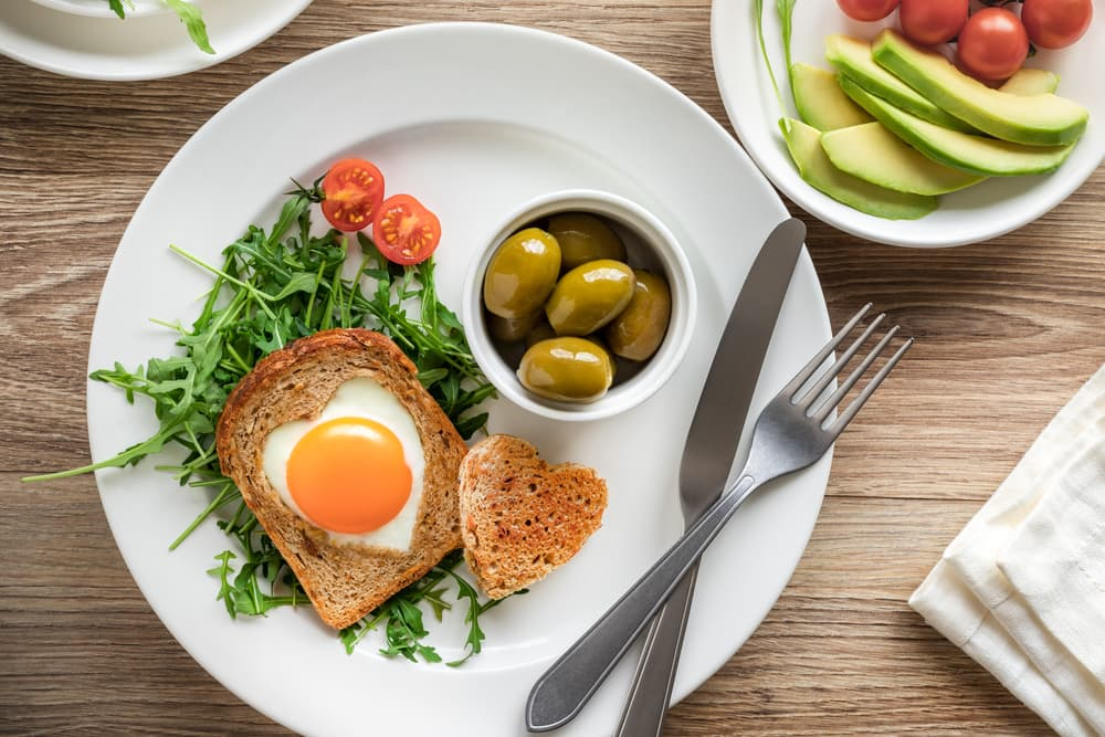 olives, egg and toast on a bed of rocket