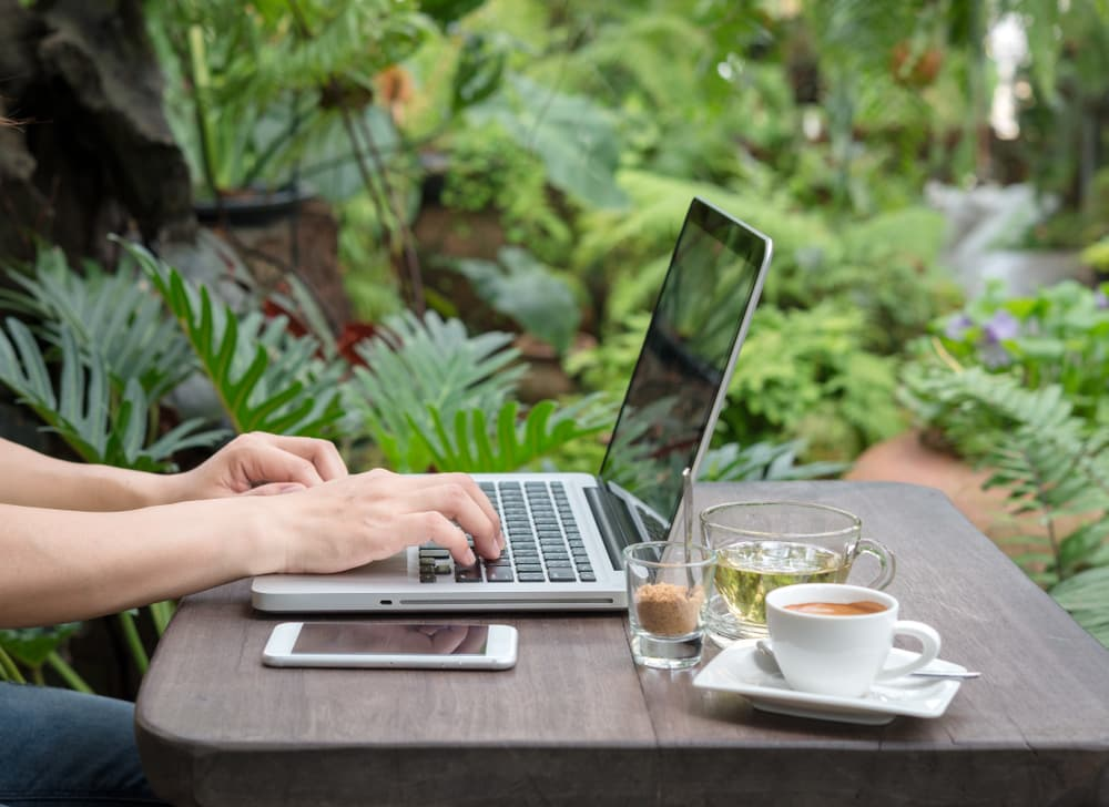 working outdoors on a desk with laptop and coffee