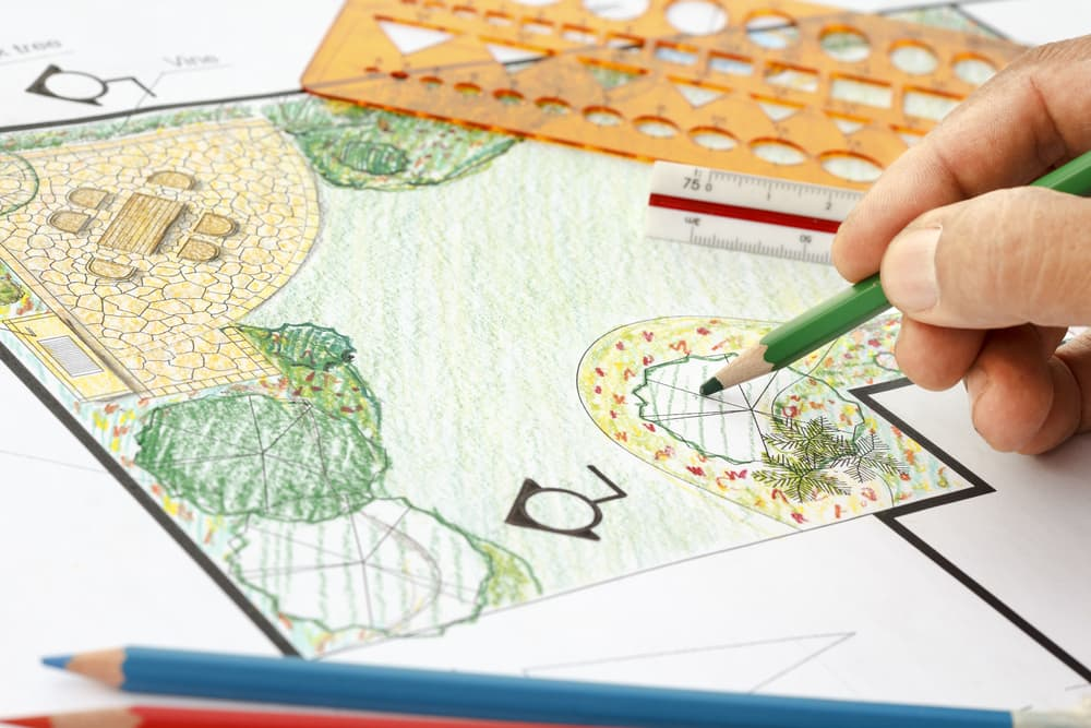 a landscaper drawing out plans for a garden