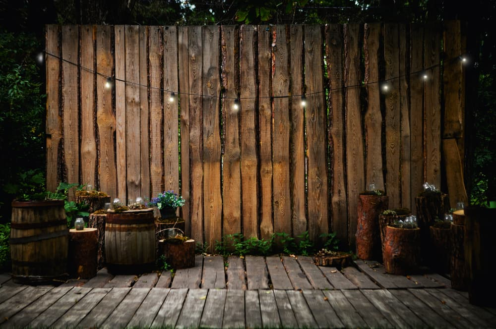 a timber wall with barrels and string lights