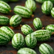multiple very small cucamelons on a wooden table