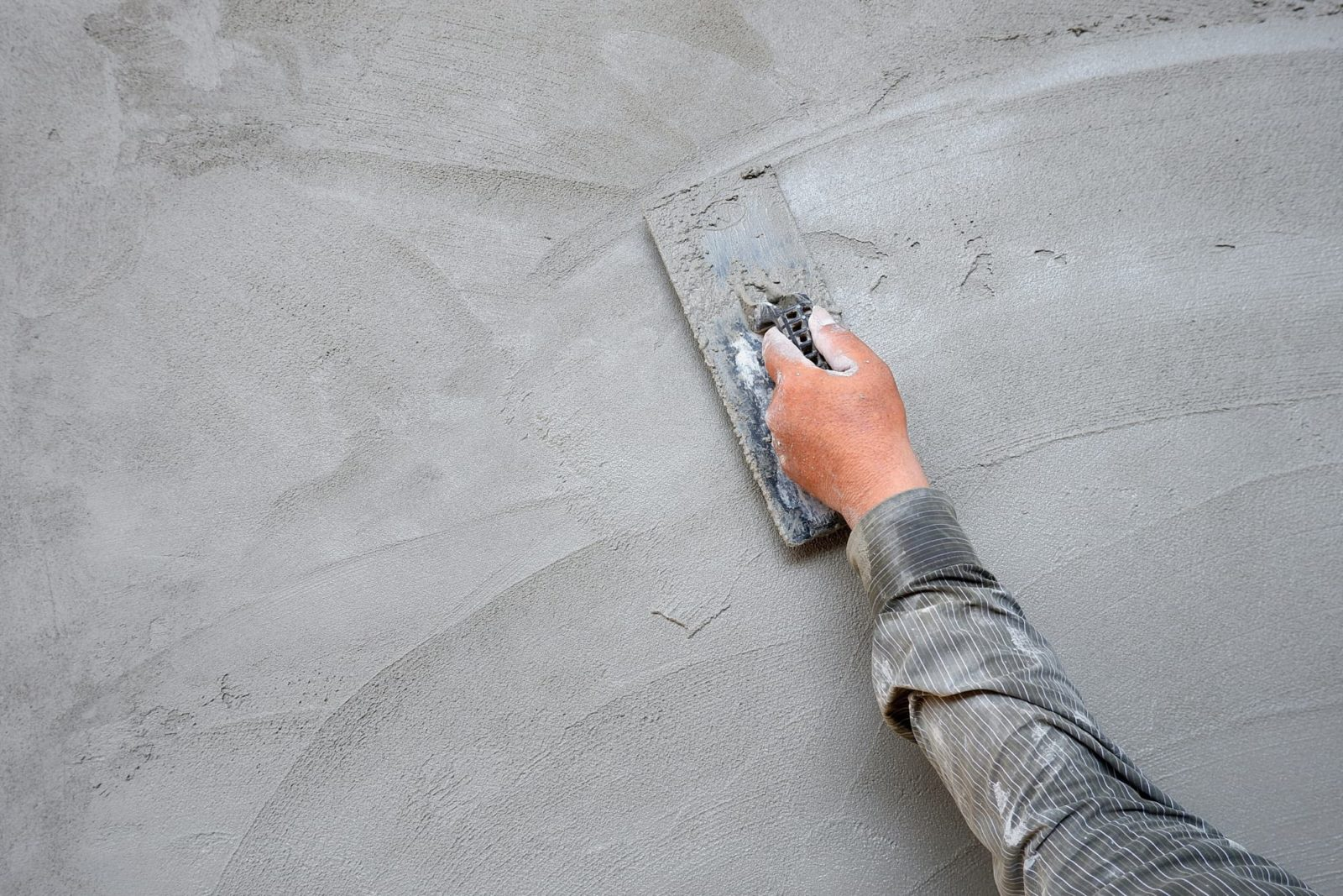 man using trowel to render an exterior wall