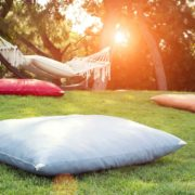 multi coloured outdoor scatter cushions sat on a lawn with a hammock in background