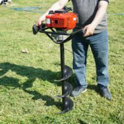 man holding an auger upright on a field